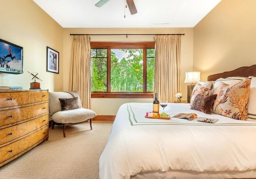 A102 Hummingbird Lodge Bedroom with windows looking out onto greenery.