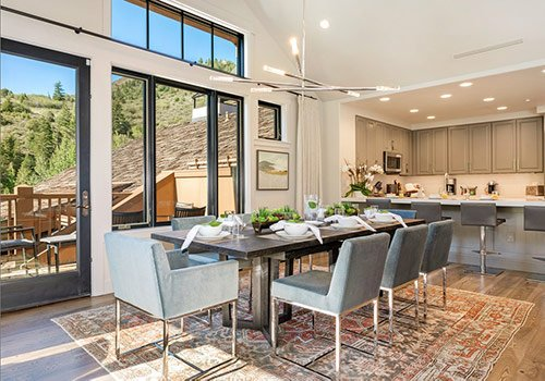 Large dining room table with balcony and kitchen in the background.